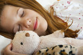 Young teenage girl sleeps peacefully with her favorite childhood toys besid — Stock Photo