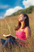 Beautiful young girl enjoys sun while sitting on the meadow and reading the — Stock Photo