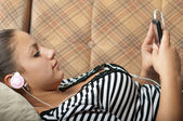Beautiful teenage girl listens to music on the mobile phone while lying on — Stock Photo