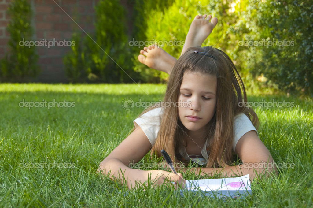 Pretty young teenage girl drawing on the paper while lying on the bed of grass.   Stock Photo #7135372