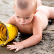 Stock Photo: Little boy playing in sand with plastic con hot summer evening.