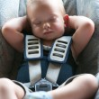 Infant boy sleeps peacefully secured with seat belts while in the car. - Stock Photo