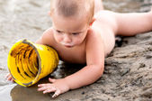 Little boy playing in the sand with plastic can on hot summer evening. — Stock Photo