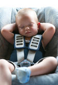 Infant boy sleeps peacefully secured with seat belts while in the car. — Stockfoto