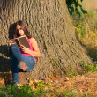 Beautiful young girl with glasses reads book while sitting under the huge t — Stock Photo #7152885