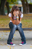 Young girl in sitting in the park — Stock Photo