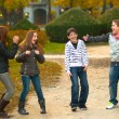 Stock Photo: Teenage boys and girls having fun in the park on beautiful autumn day