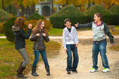 Teenage boys and girls having fun in the park on beautiful autumn day — Stock Photo