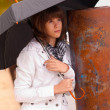 Beautiful sad teenage girl holds umbrella on cloudy autumn day — Stock Photo