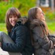 Pretty teenage girls laughing and joking while sitting in the park — Stock Photo