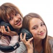 Two teenage girls listen to music together through the headphones — Foto de Stock