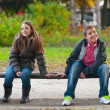 Shy boy and the girl sitting in the park and lightly touching each other fi - Stock Photo