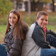 Teenage boy and girl enjoying each others company in the park on beautiful — Stock fotografie