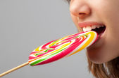 Detail of the beautiful girls face with huge lollipop between her teeth — Stock Photo
