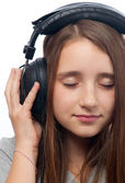Beautiful teenage girl with closed eyes listens to music through the headph — Stock Photo