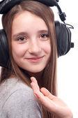 Beautiful teenage girl listens to music through the headphones — Stock Photo