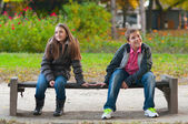 Shy boy and the girl sitting in the park and lightly touching each other fi — Stok fotoğraf