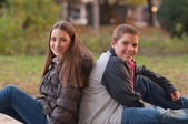 Teenage boy and girl enjoying each others company in the park on beautiful — Stok fotoğraf