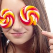 Beautiful teenage girl hiding her eyes with lollipops — Stock Photo