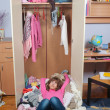Untidy teenage girl lying on pile of wrinkled clothes inside her wardrobe - Stock Photo