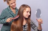 Ziemlich weibliche teenager haare zu kämmen und beobachten sich selbst im spiegel — Stockfoto
