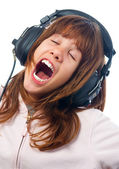 Beautiful teenage girls sings while listening music through headphones — Stock Photo