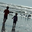 Stock Photo: Two Kids Playing on Beach as Sun is Glistening on Water