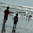 Two Kids Playing on the Beach as the Sun is Glistening on the Water - Stock Photo