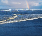 Ocean Waves Breaking on Shore with a Partial Rainbow in the Background — Stock Photo