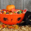 Black cat protecting halloween candy — Stock Photo