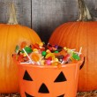 Candy filled halloween pumpkin bucket — Stock Photo