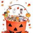 Halloween pumpkin bucket with candy and falling  leaves — Foto Stock