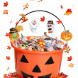 Halloween pumpkin bucket with candy and falling  leaves — Stok fotoğraf