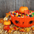 Bowl of halloween candy with fall leaves — Stock Photo