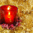 Foto Stock: Red candle in gold garland