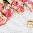 Stock Photo: Wedding bands with bunch of roses