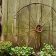 Old wagon wheel leaning on barn — Stock Photo