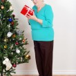 Foto Stock: Happy senior womwith christmas gift