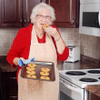 Senior woman eating fresh cookie — Stock Photo