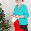 Senior woman filling christmas stocking — Stock Photo #7688216