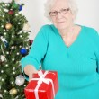 Foto Stock: Senior womgiving christmas present