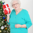 Senior womguessing her christmas gift — Stock Photo #7688230