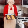 Senior woman with fresh baked cookies — Stock Photo