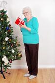 Happy senior woman with christmas gift — Stock Photo