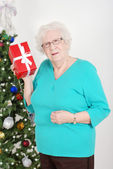Senior woman guessing her christmas gift — Stok fotoğraf
