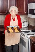 äldre kvinna med färskt bakade cookies — Stockfoto