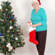 Senior woman with santa hat and stocking — Stock Photo