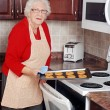 Senior woman with tray of fresh baked cookies — Stock Photo