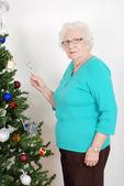Mujer senior colgantes bastón de caramelo en árbol de navidad — Foto de Stock