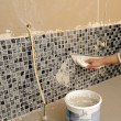 Home improvement - grouting mosaic tiles. — Stock Photo